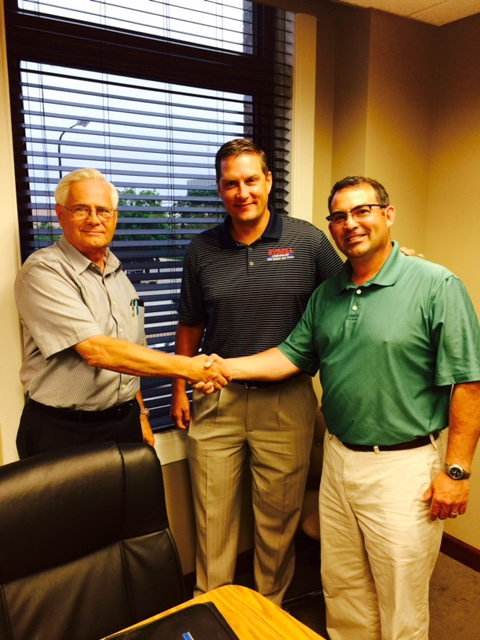 Dealership buyers Jim Rydell and Matt Halbur pose with seller John Butler.
